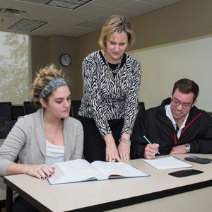 Teacher assisting students during an in-class assignment in an accounting class