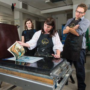 Teacher, Michelle Martin, demonstrates print making in class.