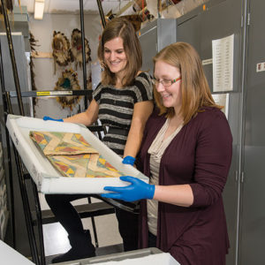 two women in gloves handle a tray with museum artifacts