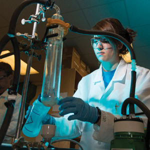 a female student measures a solution as fluid pumps into a glass cylinder in the chemistry lab