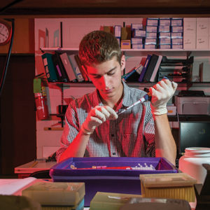 a male student carefully measures samples with a syringe before placing them in a well tray as he sits in the biology lab