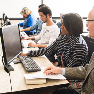 a group of students in the computer lab being assisted by an analytics teacher