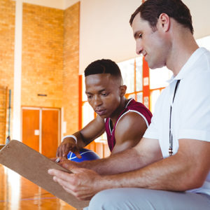 a coach uses a clipboard to describe plays to a basketball player