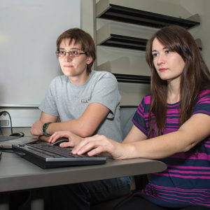 a male and female student pair program, she is typing into a computer as he sits next to her and observes the work