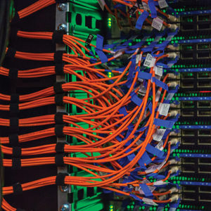 a close up shot of a server rack, thick orange cords flow seamlessly into blue outlets, illuminated by a soft green light