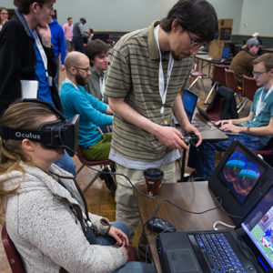 a student wears an Oculus Rift as another uses a handheld controller to play a video game at the Heartland Gaming Expo