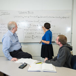 A female student leads a professor and peer through the solution of a fairly long equation on a white board