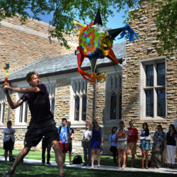 spanish students having fun with a piñata outside on campus.