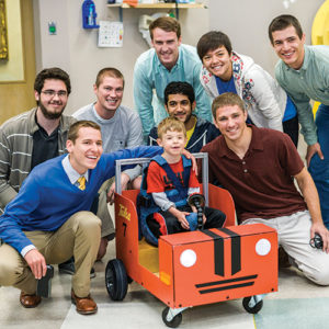 Mechanical engineering students pose around a boy driving a small cart they designed and built for the Little Light House