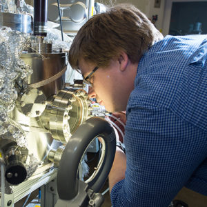 a student leans in closely to inspect the opening of a large piece of equipment