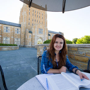 sociology student studying outside of McFarlin library on campus during the afternoon