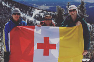 Members of Kappa Alpha Order men's fraternity pose on a snowy mountain top holding their fraternity flag proudly.