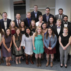 students from the Newman Center stand for a photo after a formal event