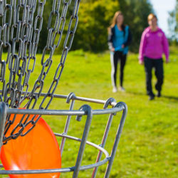 a discgolf net holds a frisbee as two students approach