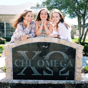 Chi Omega members smile in front of their sorority house