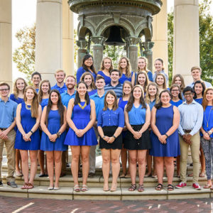 Students in the Future Alumni Council in all blue clothing in front of the TU bell on campus.