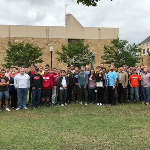 Students in IEEE pose in front of a building on TU's campus
