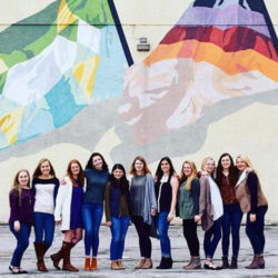 Kappa Kappa Gamma members pose in front of a downtown mural