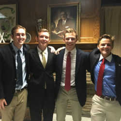 Lambda Chi fraternity members smile in their fraternity house
