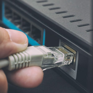 A close up look at a LAN internet chord being plugged in.
