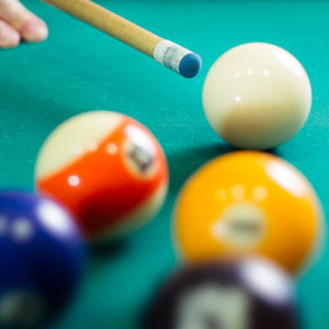 Close up view of a pool table, pool balls, and a cue.