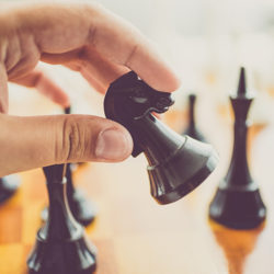 A close up view of someone moving a black chess game piece on the board.