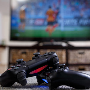 A close up view of Playstation controllers in front of a large flatscreen television displaying a sports game.