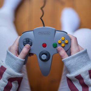 A close up view of a Nintendo 64 controller being held by a gamer.
