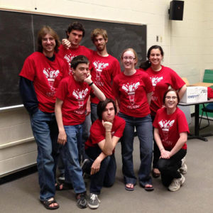 Spiked Punch Lines members posing in their improv shirts all together in a classroom.