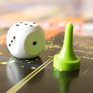 A close up view of a single traditional die and lime green playing piece on top of a board game.