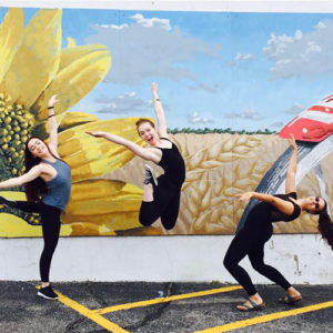 Terpsichore members show of their dance moves in front of an Oklahoma themed mural.