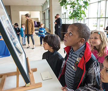 children look upon artwork at the Humanities Festival
