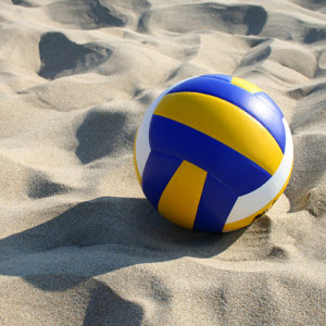sand volleyball court with a blue, yellow and white volleyball