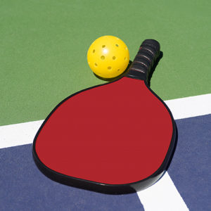 yellow pickleball and red paddle