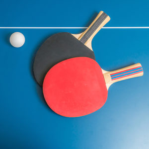 two paddles and one ball sitting on a blue tennis table