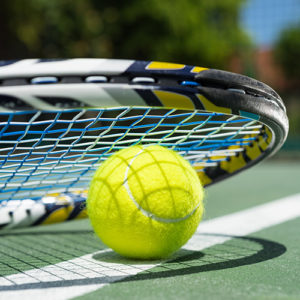 close up view of a tennis ball and racket sitting on a tennis court outside