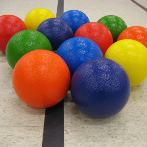 various brightly colored dodgeballs sitting on the ground