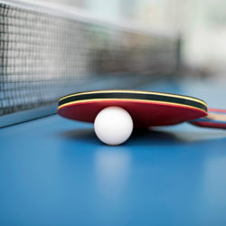 close up view of a racket and ping pong ball on a tennis table