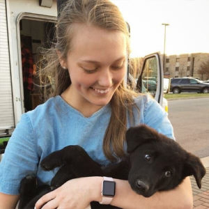 TU Students for Animal Welfare member (Sam) hold an adorable puppy while at an event on campus