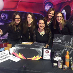 Phi Alpha Delta members at a booth featuring a Harry Potter themed booth.