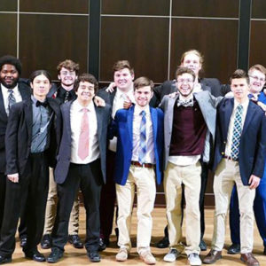 Phi Mu Alpha members take a group photo while dressed up for a concert they are about to perform in the LPC on campus.
