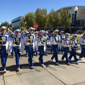 Sound of the Golden Hurricane marching band walking to the football game on game day in full uniform with instruments.