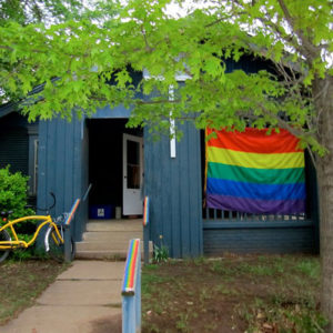 "The ""little blue house"" shown displaying a pride flag"