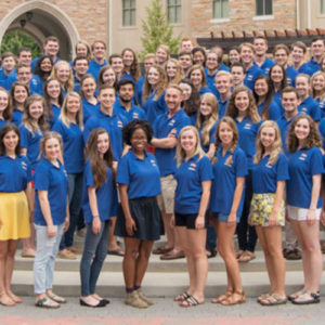 University Ambassadors standing all together in their blue tour shirts on a sunny day on campus