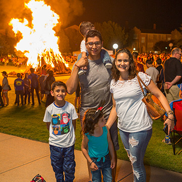 A family smiles, illuminated from behind by the Homecoming Bonfire