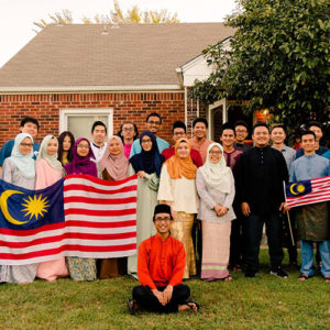 Malaysian students in MASA group together outside a gathering and celebration holding up Malaysian flags.