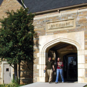 Two students walking out of the main entrance of John Mabee Hall on campus.