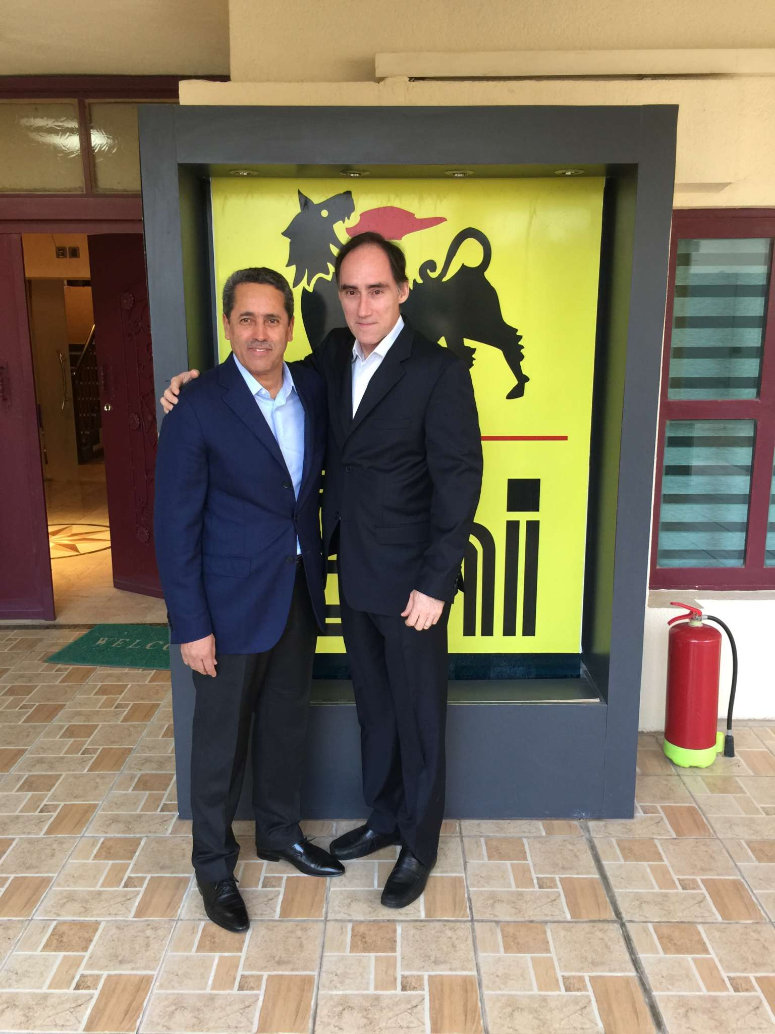 Professor Buford and a colleague wearing suits and standing in front of a yellow and black Eni company sign