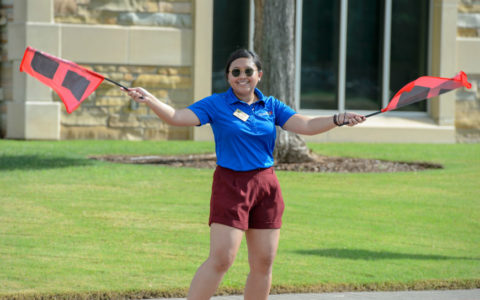 Young woman in a blue polo shirt waving University of Tulsa hurricane flags