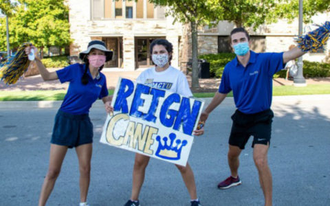 Three students with a Reign Cane sign